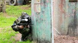 Boy paintball player sits in ambush behind metal fence and looks poster