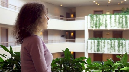 Woman stand at balcony with plants in multiple floor building