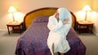 Woman in white bathrobe comes to bedroom and wipe her hair by