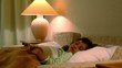 Little girl lies in bed with eyes open at background of lamp