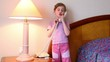 Little girl stand and talk phone in room with lamp near bed