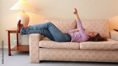 Young woman lies on sofa and dances at room with lamps on each