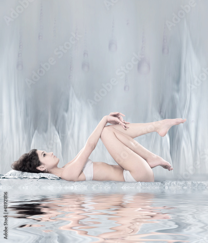 A woman laying in lingerie on a light grey abstrack background