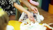 child-minder lays out pieces of cake to kids sitting at table in