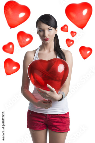 sexy brunette with heart shaped balloon in front of the camera