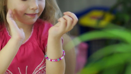 Child making jewelry from beads. Looking at camera