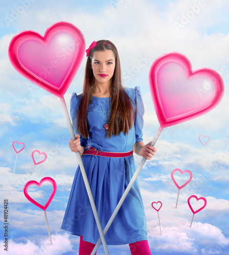 Beautiful woman holding  two hearts over a sky background