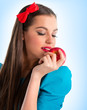 Young beautiful woman in blue holding a red apple