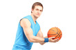 A male basketball player with basketball looking at camera