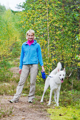 The woman with a dog walk in an autumn wood