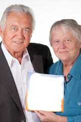 Senior couple showing book with copy space