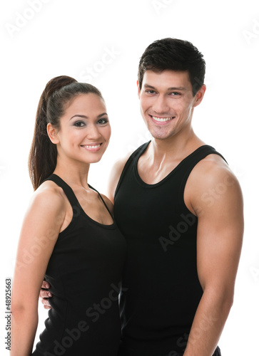 Two sportive people in black sportswear embrace each other