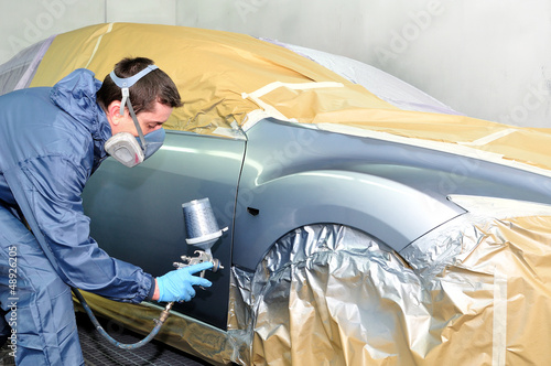 Worker painting a car.