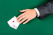 Hand with aces on the green table. Challenge to the casino