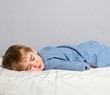 Little boy in blue pyjamas sleeping in bed