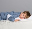 Playful little boy wearing blue pyjamas in bed