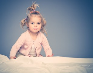 Little girl having fun on bed