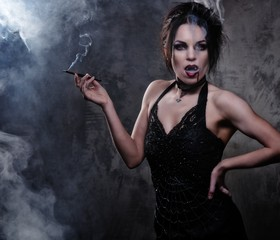 Beautiful vampire woman in black dress smoking