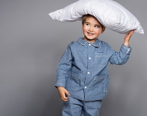 Little boy in blue pyjamas with pillow