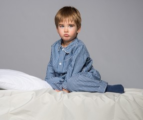 Disappointed little boy in blue pyjamas on bed