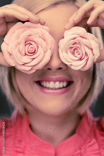 Happy blond woman with two rosebuds