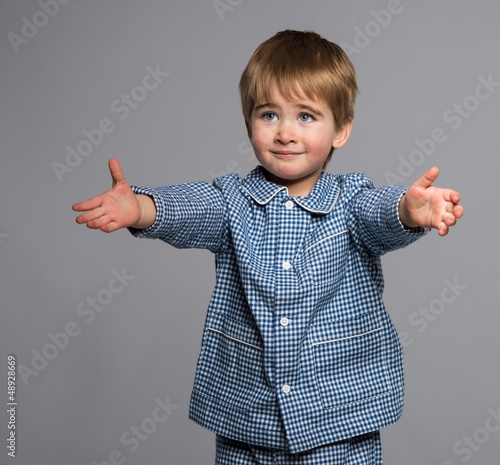 Little boy in blue pyjamas with arms wide open