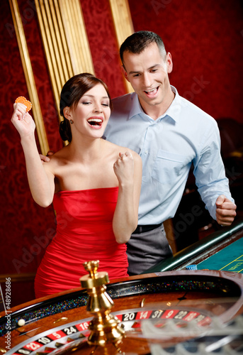 Man accompanied by woman placing bets at the casino