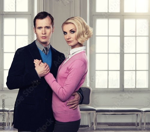 Elegant couple indoors standing near window
