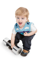 Small boy is trying to raise large dumbbell