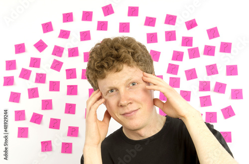 Young manpink sticky notes question marks decision making