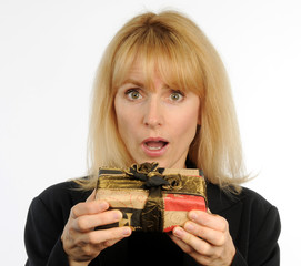 Attractive woman holding wrapped present surprised expression