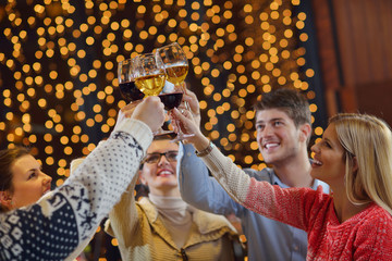 Group of happy young people drink wine at party