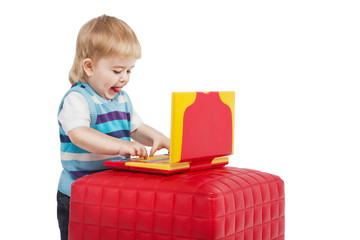 Small boy using a red and yellow laptop