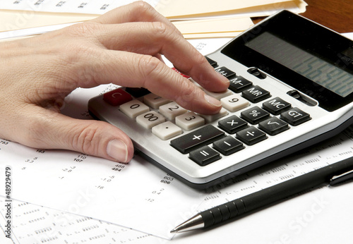 Hands on calculator  with pen and financial papers