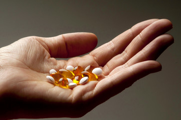 Closeup of  hand holding vitamin E and vitamin D capsules