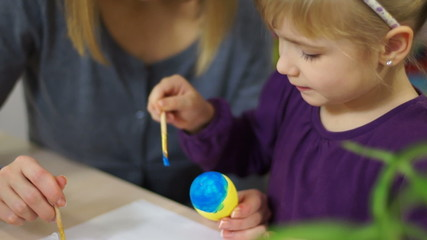Closeup portrait of a child decorating  an Easter egg