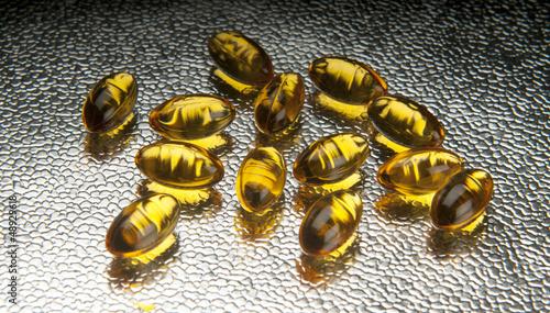 Closeup of vitamin E capsules on metallic background