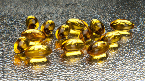Closeup of vitamin E capsules on metallic background