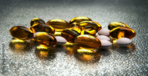 Closeup of vitamin E and D capsules on metallic background