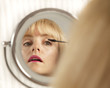 Attractive blond woman applies eyeliner makeup in mirror..