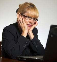 Stressed female executive hands on face looking at computer