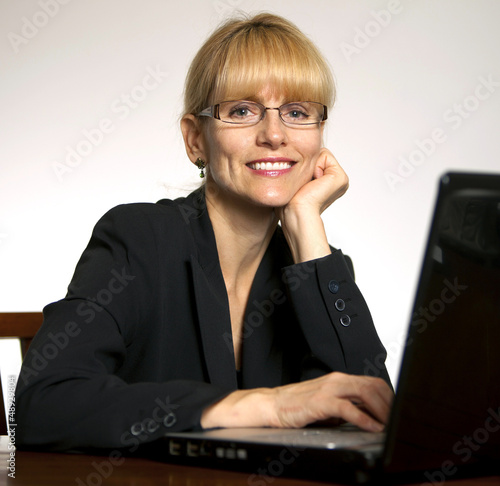 Happy, smiling female executive office with hands on computer