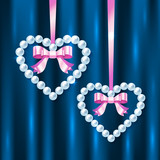 Pearl hearts with pink ribbons and bows on dark blue silk