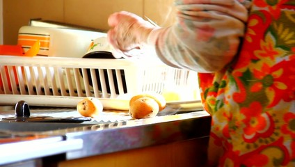 Elder woman preparing potato.