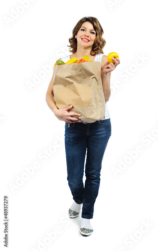 Young girl with fruits in paper bag isolated on white