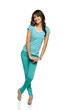 Full length of flirty female in turquoise pants and t-shirt
