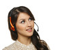 Smiling woman in headset looking to the side at blank copy space