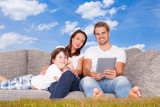 family in nature with tablet