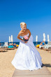 Young blonde bride on beach and blue sea