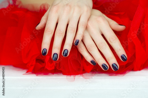 Closeup dark manicure on red